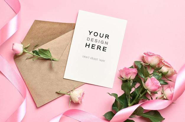Mockup di carta invito a nozze con busta e bouquet di fiori di rose sul rosa