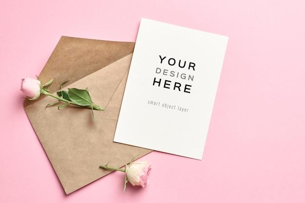 Mockup di carta invito a nozze con busta e fiori di rose sul rosa