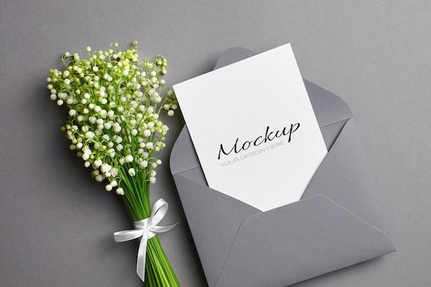 Invito a nozze o modello di biglietto di auguri con busta e bouquet di fiori di mughetto