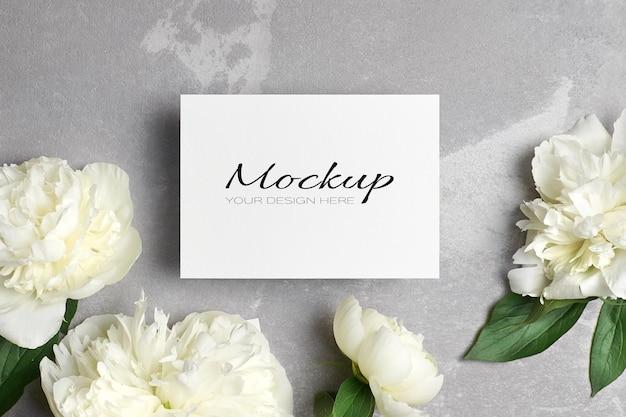 Invito a nozze o modello di biglietto di auguri con busta e fiori di peonia bianca su grigio
