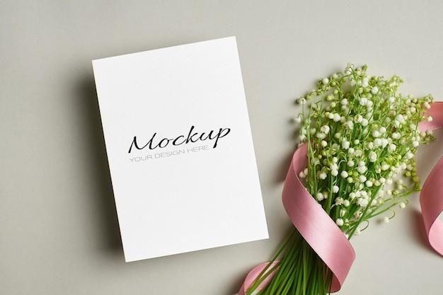 Invito a nozze o modello di biglietto di auguri con bouquet di fiori di mughetto con nastro rosa