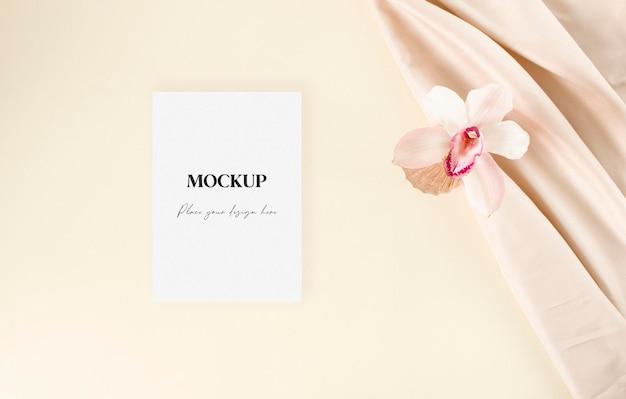 Carta mockup di invito a nozze con giglio e tessuto nudo sullo sfondo beige vista piatta