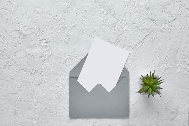 Carta in bianco bianca in busta sul fondo del cemento. modello.