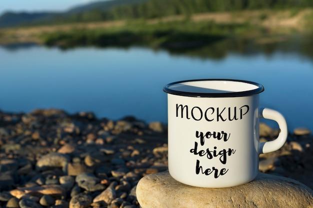Mockup di tazza di smalto falò bianco con fiume blu