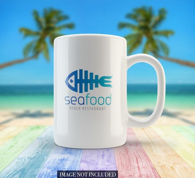 Vista frontale del modello della tazza da caffè bianco sulla spiaggia
