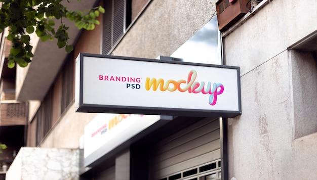 Modello di cartello commerciale bianco per il design del logo su un muro di un negozio in strada Psd Premium