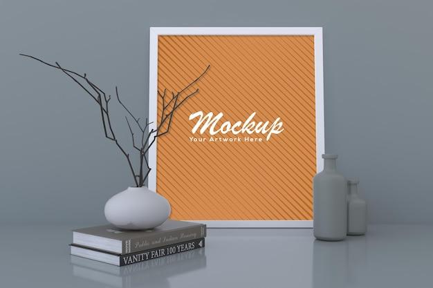 Mockup di cornice per foto vuota bianca con vasi e libri