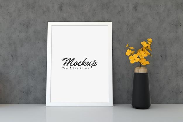 Mockup cornice bianca con vaso di fiori gialli