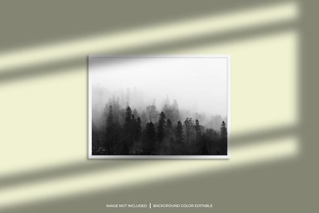 Mockup di cornice per foto orizzontale bianca con sovrapposizione di ombre e sfondo di colore pastello