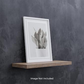 Mockup di cornice per foto bianca su mensola in legno