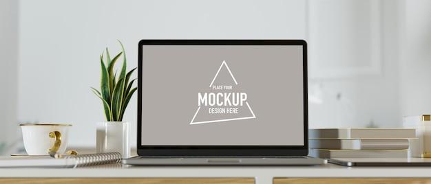Modello del computer portatile dello schermo bianco con la tazza da caffè della piccola pianta dei libri sul fondo bianco del tavolo da lavoro accogliente