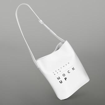 Mockup di borsa a tracolla bianca su sfondo grigio