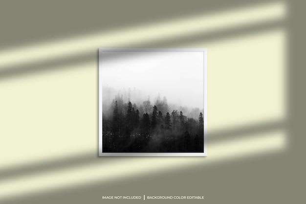 Mockup di cornice per foto quadrata bianca con sovrapposizione di ombre e sfondo di colore pastello