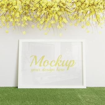 Mockup bianco cornice verticale in piedi sull'erba artificiale verde