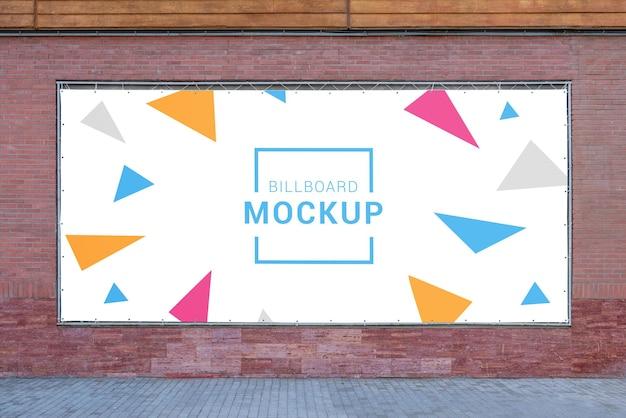 Mockup di tabellone per le affissioni su tela cerata larga sul muro di mattoni
