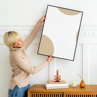 Donna che appende una cornice per foto su un modello di muro bianco
