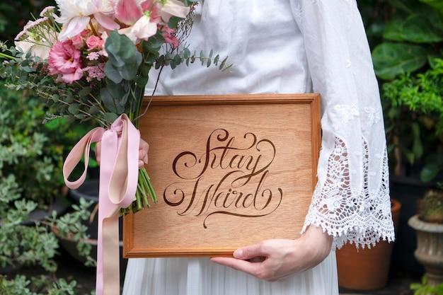 Donna che tiene un mazzo di fiori con una tavola di legno