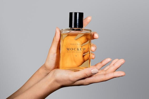 Donna che tiene un modello di psd della bottiglia di vetro del profumo