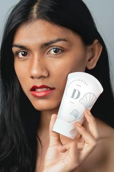 Donna che tiene un mockup di contenitore per crema viso bianca