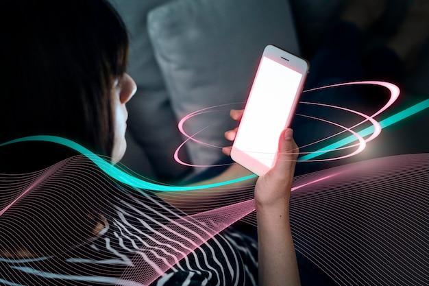 Donna che gioca con il telefono mentre è sdraiata sul divano