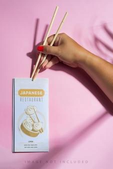 La mano della donna tiene il mockup dell'opuscolo con bastoncini di legno.