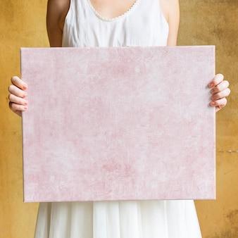 Donna che mostra una tela bianca