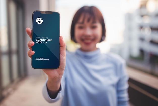 Donna che mostra il suo mockup dello schermo dello smartphone