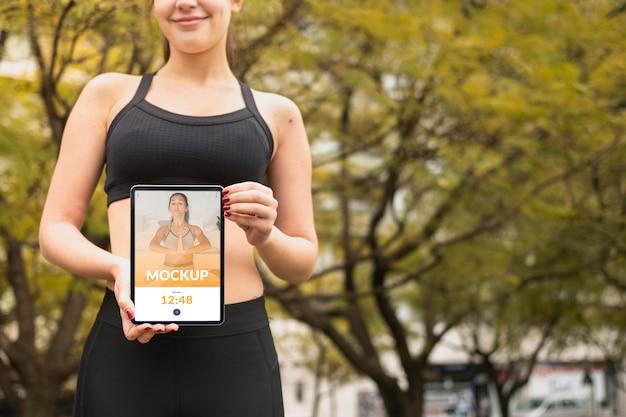 Donna in abiti sportivi che tiene il modello di tavoletta digitale