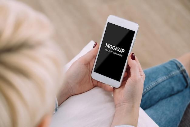 Donna che utilizza smartphone mockup mentre è seduto sul divano