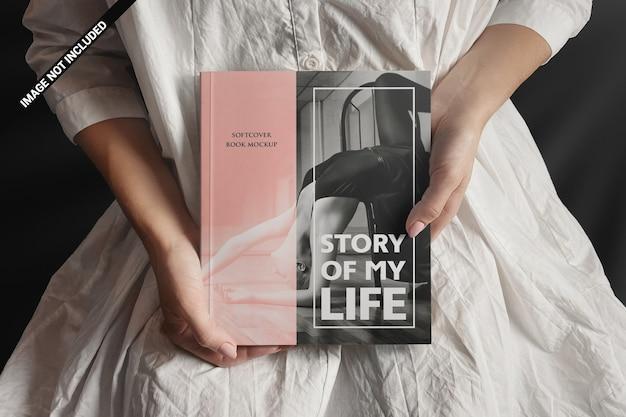 Donna in bianco che presenta un mockup di libro