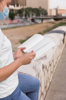 Donna con maschera leggendo il libro sulla strada