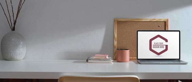 Posto di lavoro con laptop mockup e moodboard