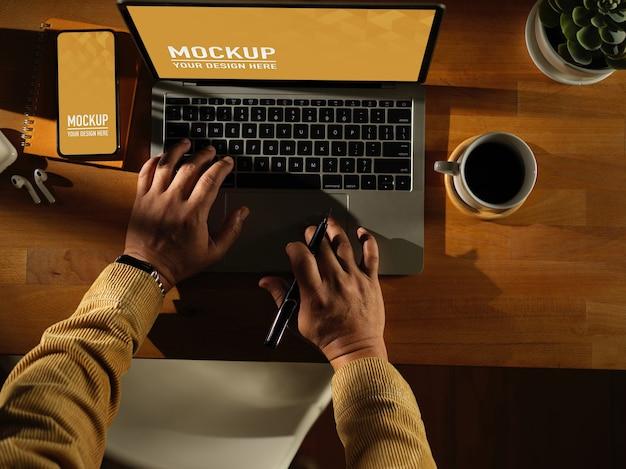 Area di lavoro con telefono digitale e mockup di laptop con tazza