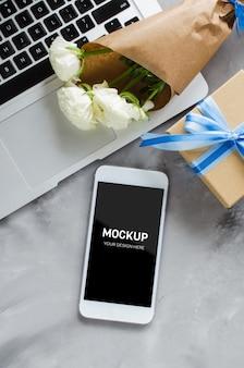 Area di lavoro con computer portatile, schermo dello smartphone mock up, confezione regalo e fiori.