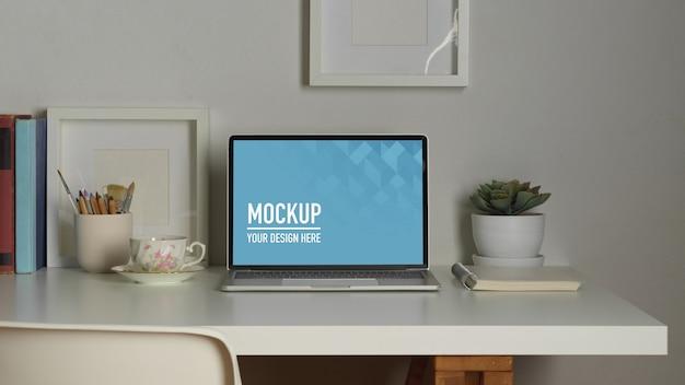 Area di lavoro con mockup di laptop, libri e articoli di cancelleria