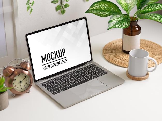 Area di lavoro con mockup di laptop e vaso per piante nella stanza dell'home office