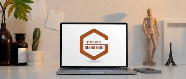 Area di lavoro con laptop mockup, smartphone e decorazioni