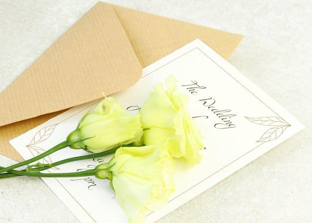 Rose gialle, busta e carta di invito su sfondo grigio
