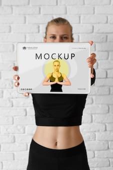 Istruttore di yoga che tiene un modello di tablet