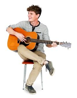Giovane uomo adulto che si siede giocando il ritratto dello studio della chitarra