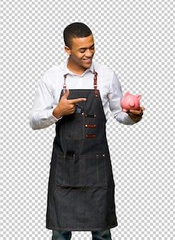 Giovane uomo afroamericano del barbiere che tiene un porcellino salvadanaio