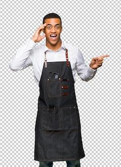 Giovane uomo afro american barbiere che punta il dito verso il lato e presentare un prodotto