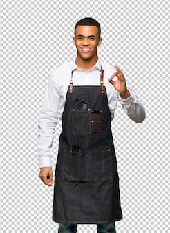 Giovane uomo afroamericano di barbiere che mostra un segno giusto con le dita