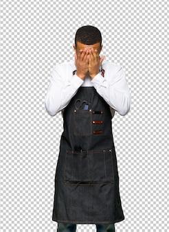 Giovane uomo afro american barbiere con espressione stanco e malato