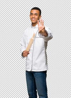 Giovane uomo afro american chef felice e contando tre con le dita