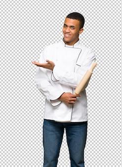 Giovane uomo afro american chef presentando un'idea mentre guardando sorridente verso