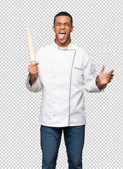 Giovane uomo afro american chef mostrando la lingua alla fotocamera con sguardo divertente