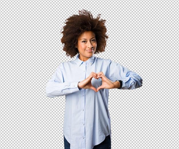 Giovane donna di colore che fa simbolo del cuore