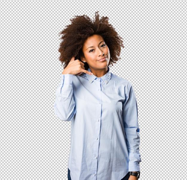 Giovane donna di colore che fa gesto di telefono