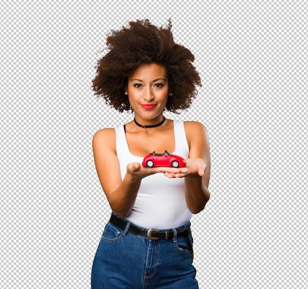 Giovane donna di colore che tiene un'automobile rossa